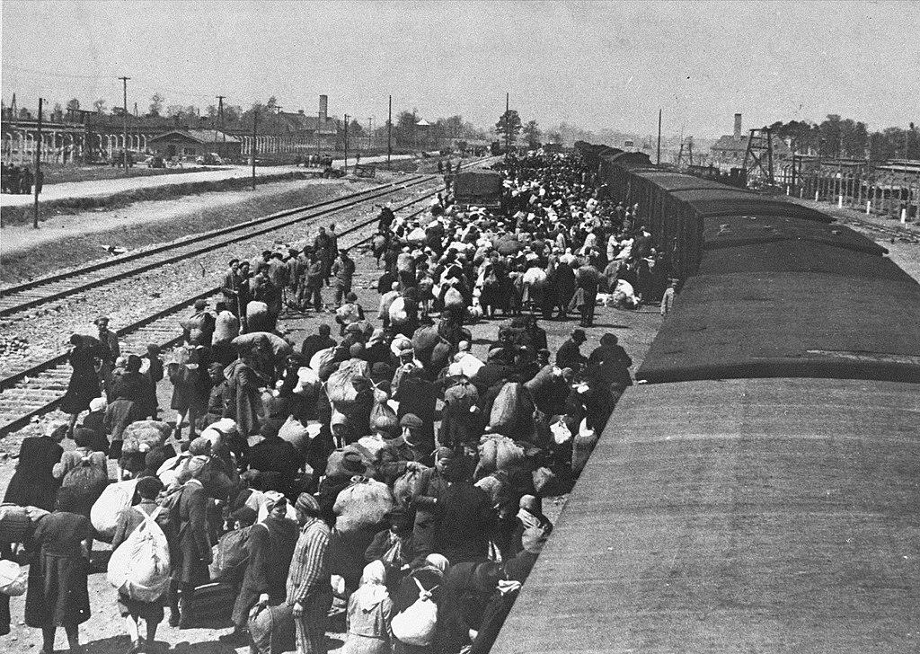 Rampe bondée d'Auschwitz-Birkenau en mai 1944. Les cheminées à l'horizon sont les crématoires situés à côté des chambres à gaz.