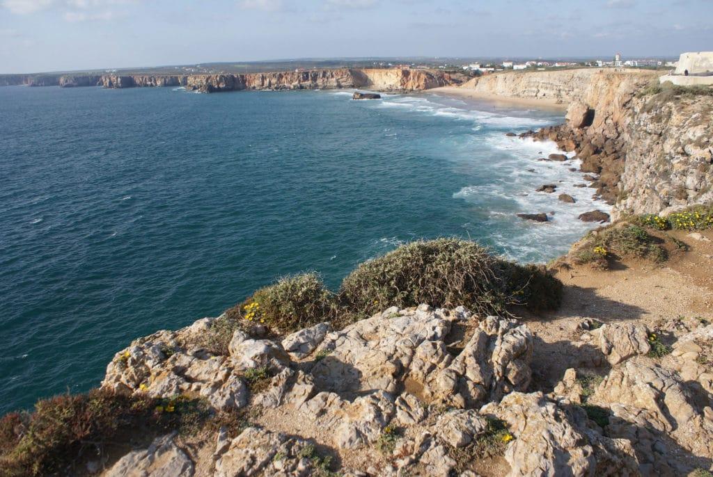 Vue depuis la forteresse de Sagrès sur un paysage typique de la région de l'Algarve, des falaises abruptes interrompues par des plages de sables fin.