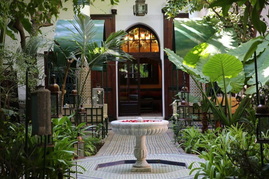 Fontaine aux fleurs dans le jardin luxuriant du Palais Riad Lamrani à Marrakech.