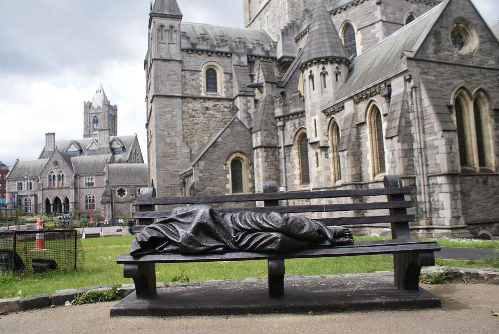 Statue devant la cathédrale Christchurch à Dublin représentant un sans abri portant les stigmates du Christ.