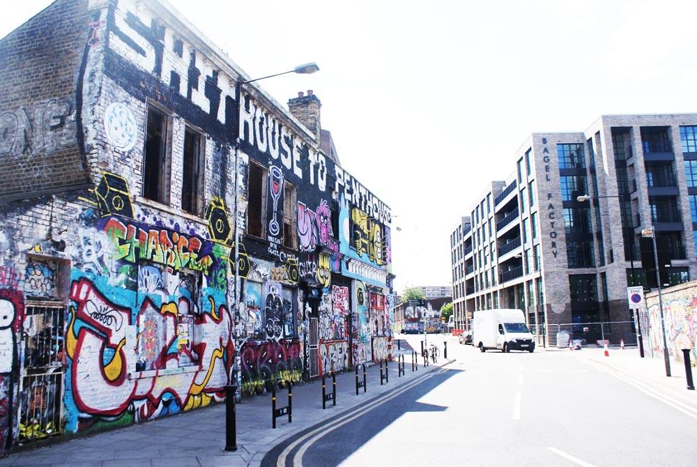 Street art dans le quartier d'Hackney Wick à Londres : A droite un ancien squat, à gauche un immeuble luxueux nouvellement construit.