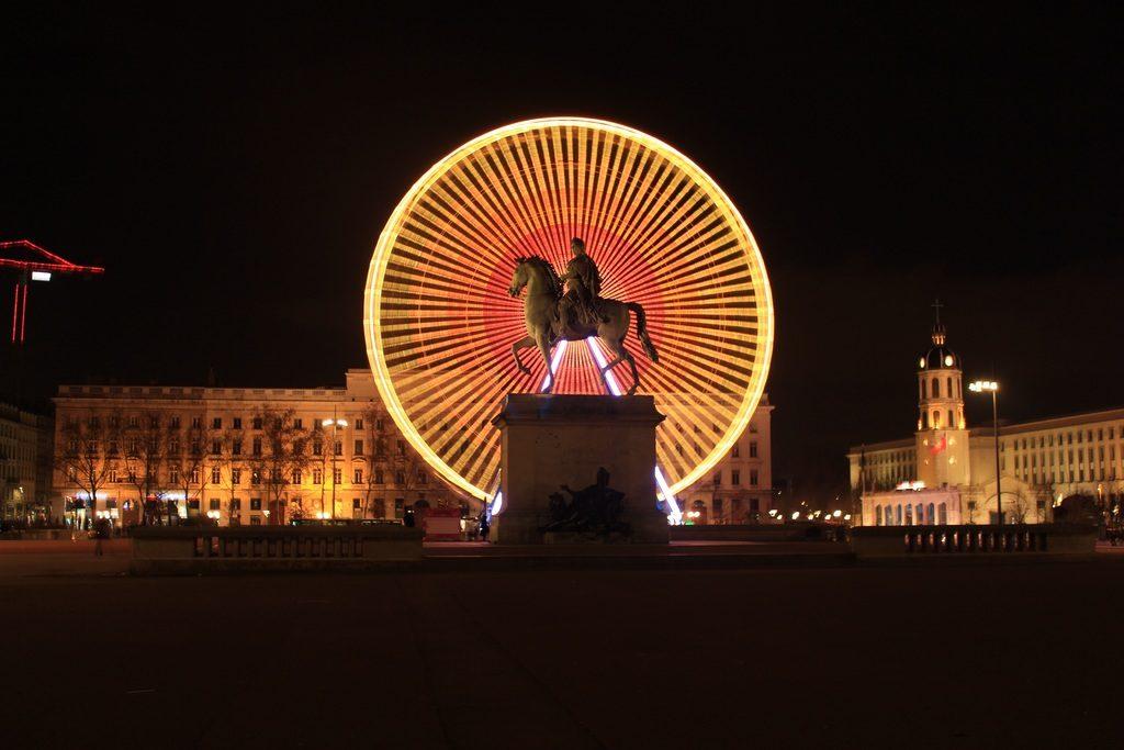 Monument à Lyon : La statue du Roi Soleil devant la grande roude illuminée de la place de Bellecour.