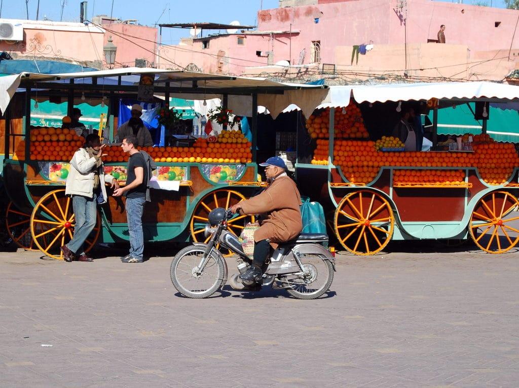 Pratique à Marrakech : Un homme en scooter devant les vendeurs de jus de fruits .