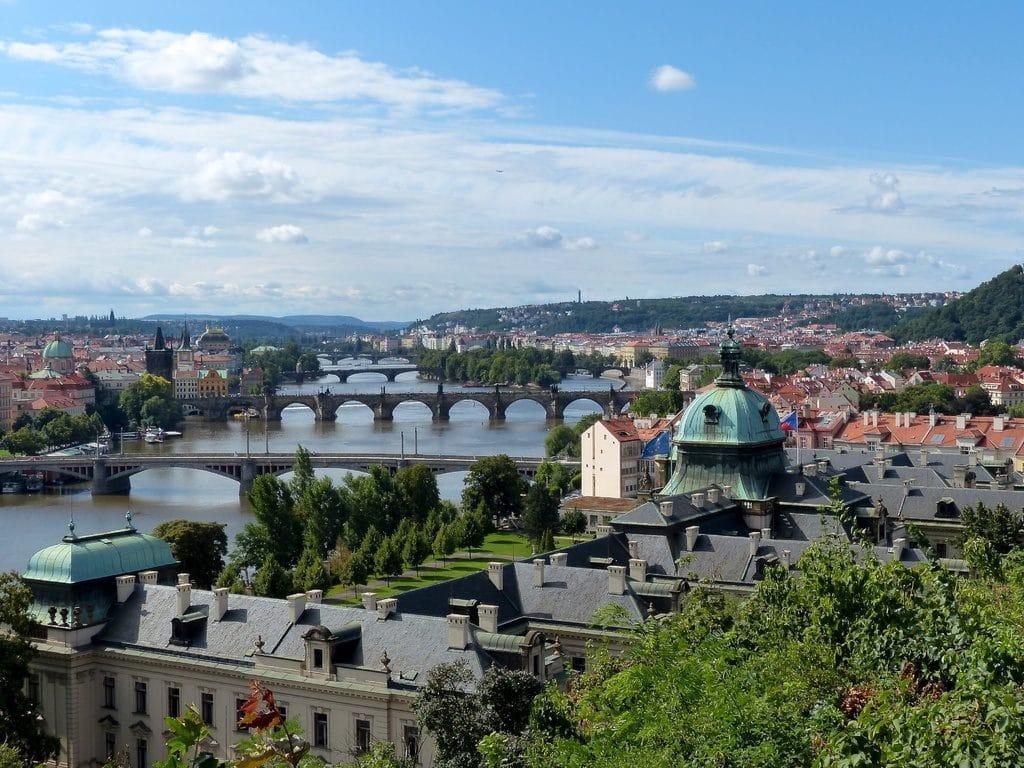Vue sur les ponts de Prague et ses collines verdoyantes.